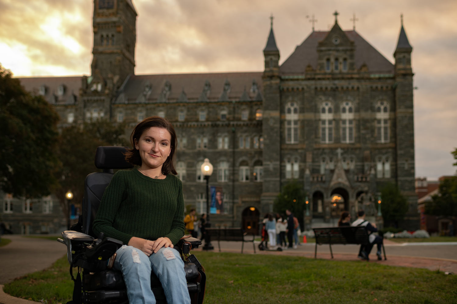 Woman in wheelchair in front an old brick building on a college campus.