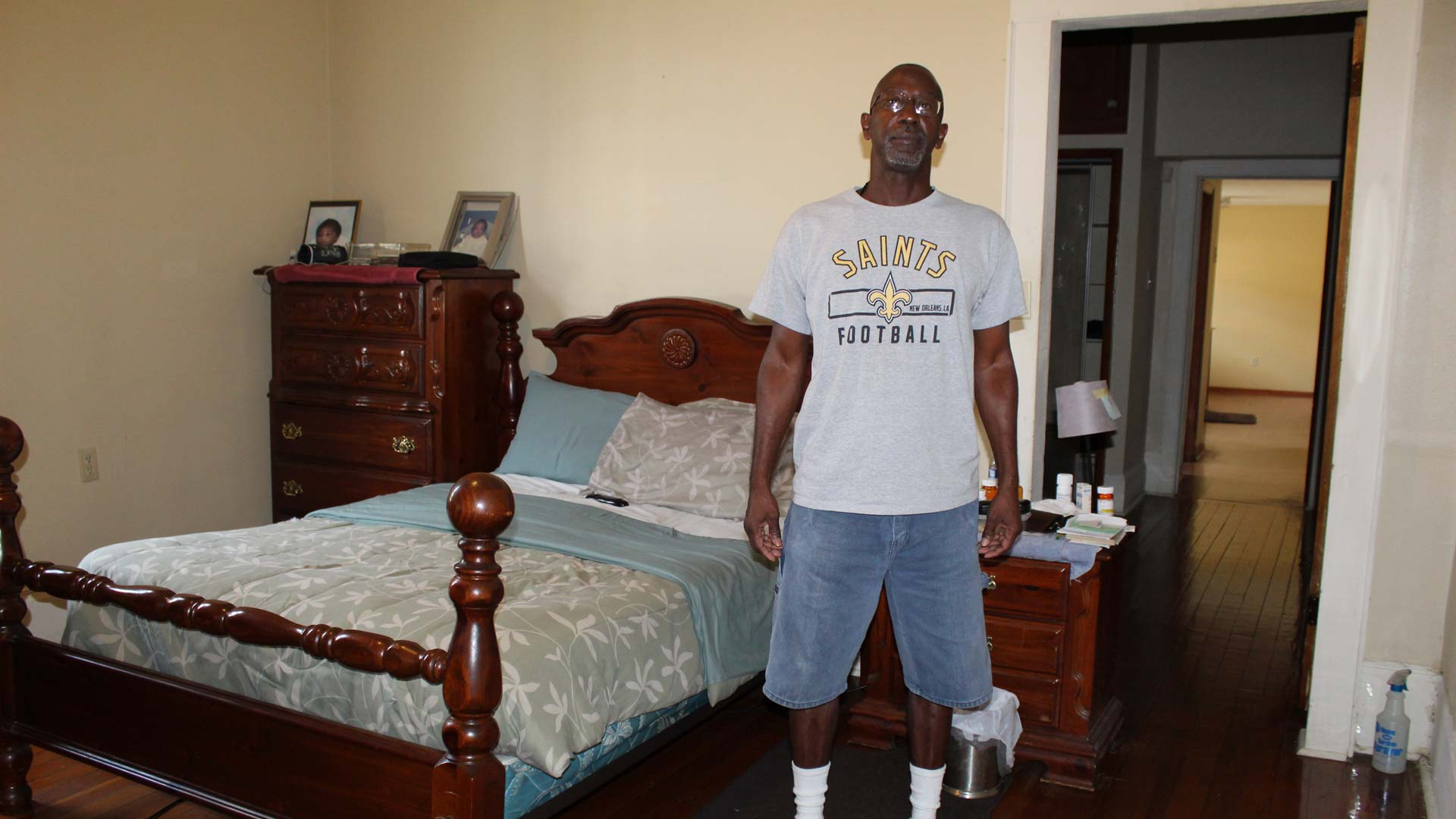 Man wearing shorts and a New Orleans Saints t-shirt stands in his bedroom.