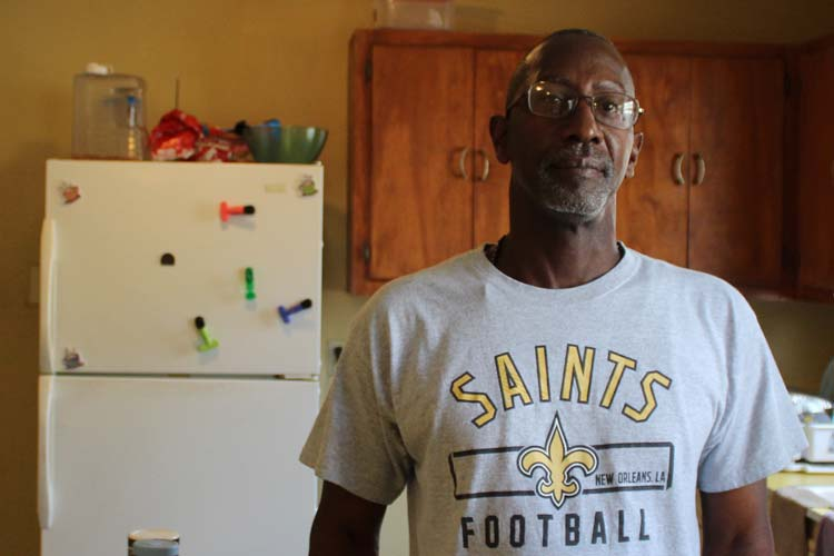 Man with New Orleans Saints t-shirt standing in his kitchen