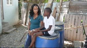 Melissa Noel stands and interviews Te-John, a child, who sits on a barrel.
