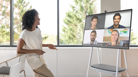 A woman presents remotely to 4 people on a Surface Hub.